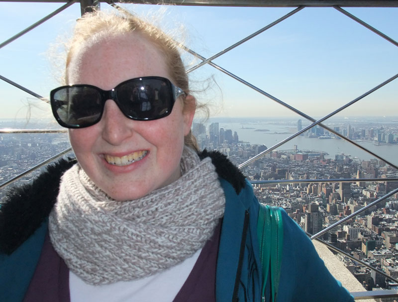 Becky atop the Empire State Building, with Ellis Island and the Statue of Liberty as a backgdrop
