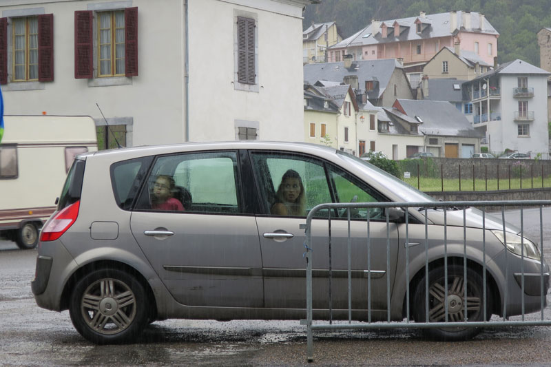 While we're eating lunch in the pouring rain, this woman is looking worried, from the comfort of her car, about her husband getting wet while ordering their lunch.