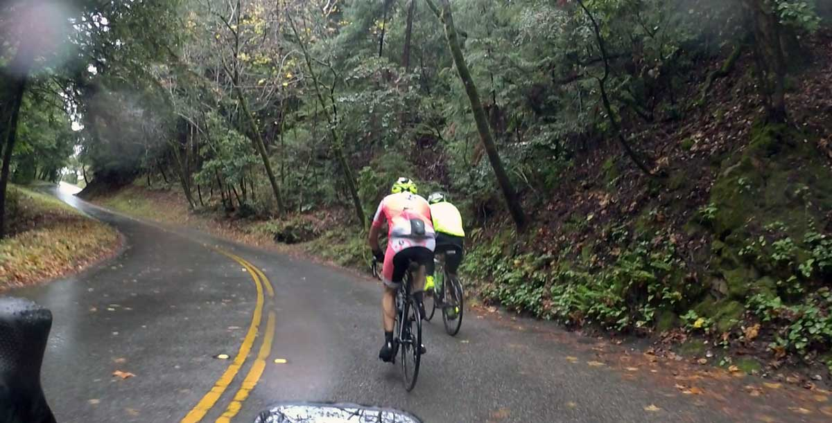The guy riding next to Kevin is out in the cold & rain with nothing on his knees?